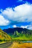 Camino que desaparece apagado en las montañas escénicas Imagen de archivo libre de regalías
