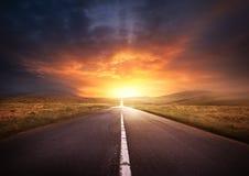 Camino que lleva en una puesta del sol Foto de archivo