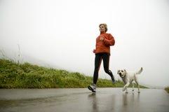 Camino que se ejecuta con el perro Foto de archivo libre de regalías