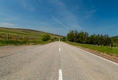 Camino recto largo en montañas escocesas Imagenes de archivo