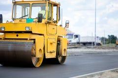Camino-rodillo anaranjado en la reparación del camino Foto de archivo