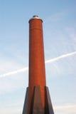 Camino rosso sulla torre alta dei mattoni verticali del cielo blu Fotografia Stock