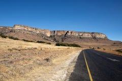 Camino rural curvado con la vista panorámica de montañas fotos de archivo libres de regalías