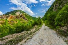 Camino rural vacío a través de clifs de la montaña fotografía de archivo