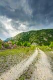Camino rural vacío a través del terreno accidentado fotos de archivo