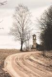 Camino temprano de la primavera, abedul y campanario viejo Foto de archivo