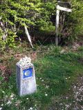 Camino trail marker with small stones on top from passing pilgrims. stock photos