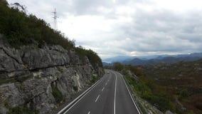 Camino a través de las colinas herbosas cantidad Camino de la montaña Día de verano nublado Recorrido en coche Bobina cruzada del almacen de metraje de vídeo