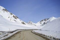 Camino a través de las montañas nevosas Fotografía de archivo libre de regalías