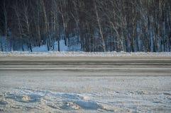 Camino urbano del paisaje del invierno al lado en las montañas y el bosque imagen de archivo