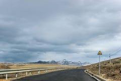 Camino vacío con la montaña del prado y de la nieve Fotos de archivo libres de regalías
