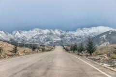 Camino vacío con la montaña del prado y de la nieve Foto de archivo libre de regalías