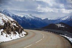 Camino vacío de la montaña en el fondo de picos nevados imagen de archivo