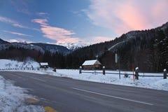Camino vacío de la montaña escénica alpina hermosa del invierno con nieve en cielo colorido de la puesta del sol en las montañas  Fotos de archivo libres de regalías
