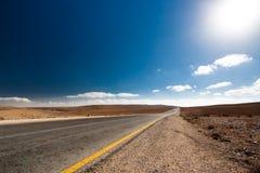 Camino vacío del desierto con el cielo azul. imagen de archivo