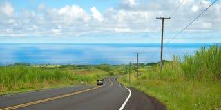 Camino vacío en campo hawaiano con el coche y el océano en backgro Foto de archivo
