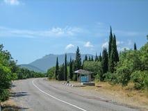 Camino vacío en el área montañoso-montañosa meridional en un día de verano caliente imagenes de archivo