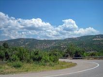 Camino vacío en el área montañoso-montañosa meridional en un día de verano caliente imagen de archivo