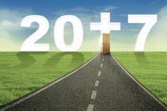 Camino vacío hacia el número 2017 con una cruz Imagen de archivo