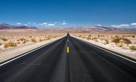 Camino vacío que corre a través del parque nacional de Death Valley Fotos de archivo