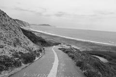 Camino vacío que lleva abajo en la playa del azkorri en el país blanco y negro, basque, España Fotografía de archivo