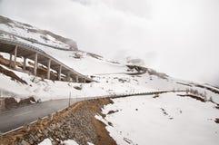 Camino vacío que lleva a través de campo, de nieve y de niebla escénicos en la montaña de Grossglockner, Austria Fotos de archivo libres de regalías