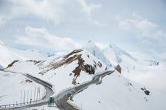 Camino vacío que lleva a través de campo, de nieve y de niebla escénicos en la montaña de Grossglockner, Austria Imagen de archivo