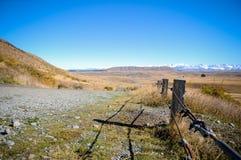 Camino vacío que lleva a través del campo escénico, cocinero National Park, Nueva Zelanda del soporte Fotos de archivo libres de regalías