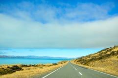 Camino vacío que lleva a través del campo escénico, Nueva Zelanda Foto de archivo libre de regalías