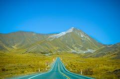 Camino vacío que lleva a través del campo escénico, Nueva Zelanda Fotografía de archivo libre de regalías