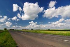 Camino vacío a través del campo con las nubes de la belleza Foto de archivo libre de regalías