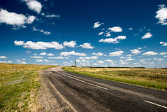 Camino vacío con una vista de campos agrícolas Fotos de archivo libres de regalías
