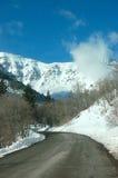 Camino ventoso a los mountians hivernales Imagen de archivo libre de regalías