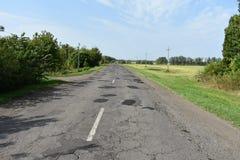 Camino viejo del asfalto de tierra del camino Fotografía de archivo