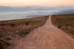 Camino y montañas brumosas Fotografía de archivo