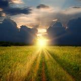 Camino y puesta del sol del campo de la suciedad Fotos de archivo libres de regalías