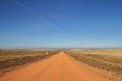 Caminos de tierra rojos en el campo Foto de archivo libre de regalías