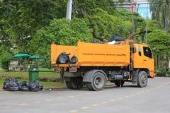 Camion à ordures avec les déchets de chargement dans le jardin de parc photos libres de droits