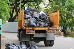 Camion à ordures avec les déchets de chargement dans le jardin de parc photos stock