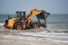 Camion avant de chargeur sur la plage dans l'eau Images libres de droits