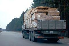 Camion avec la cargaison sciée i de bois de construction Photographie stock libre de droits