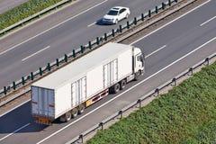 Camion blanc sur une autoroute urbaine Image stock