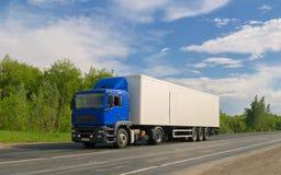 Camion blu sulla strada asfaltata sotto cielo blu con le nuvole Fotografia Stock
