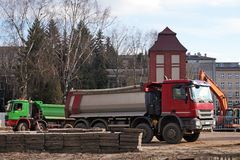 Camion che aspettano la terra da caricare dall'escavatore Mattoni che si situano all'aperto fotografie stock libere da diritti