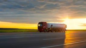 Camion che passa strada principale ad alta velocità al tramonto Immagine Stock