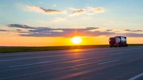 Camion che passa strada principale ad alta velocità al tramonto Fotografia Stock Libera da Diritti