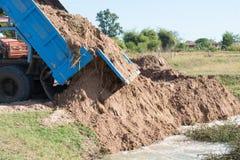 Camion che portano i campi e le paludi di bonifica del terreno Per il raggiro Fotografia Stock Libera da Diritti