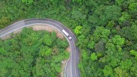 Camion che si muove lungo la strada Serpentinous curva fra l'ubriacone verde Forest Trees in Taiwan Vista superiore aerea stock footage