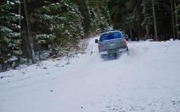 camion 4x4 che va alla deriva sulla strada della neve di inverno in foresta Fotografie Stock