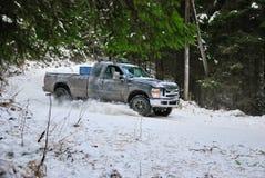 camion 4x4 che va alla deriva sulla strada della neve di inverno in foresta Immagine Stock